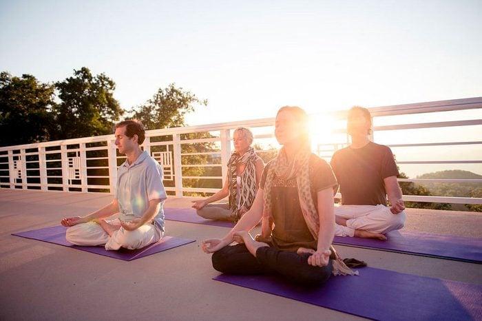 people meditating on yoga mats on a balcony area at Art Of Living Retreat Center, North Carolina