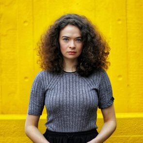 Portrait Of Woman With Curly Hair Standing Against Yellow Wall