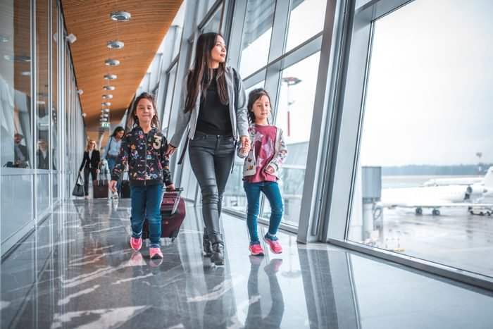Family with bare faces walking by window at airport terminal
