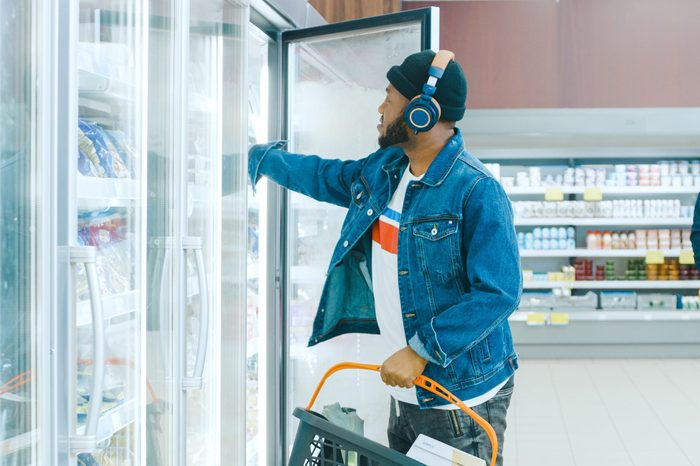 At the Supermarket: Stylish African American Guy with Headphones Chooses Products in the Frozen Goods From the Fridge and Puts them into Shopping Basket.
