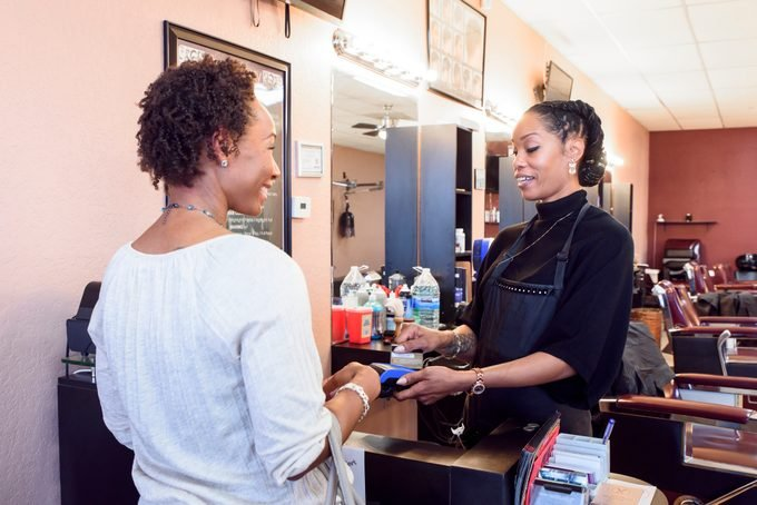 Female hairdresser taking payment from a female customer