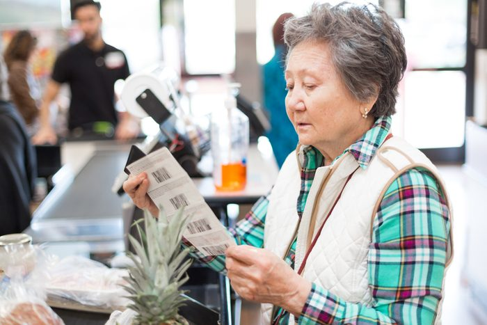 woman looking through coupons in the grocery store