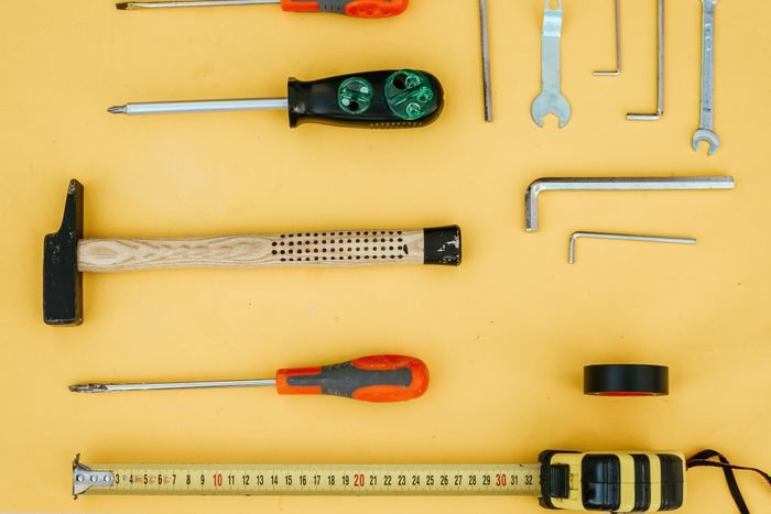 various hand tools for home improvement arranged on yellow background
