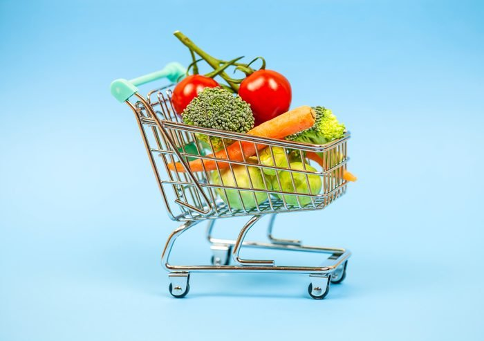 Vegetables in miniature shopping cart on blue background