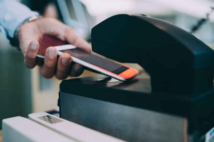 Cropped hands of businessman scanning ticket on smart phone at airport check-in counter