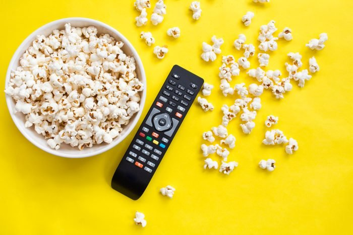 Popcorn and remote control from above on yellow background.