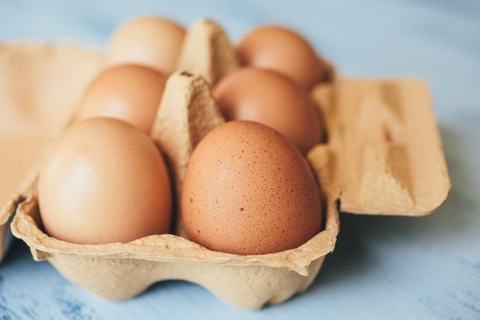 eggs with spots and bumps in a carton on a blue wood table