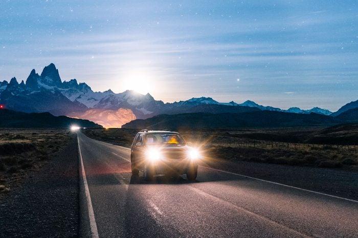 car driving at night using high beams in their headlights