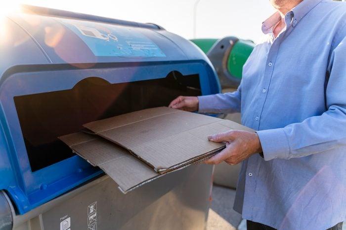 Senior man recycling cardboard in paper bank