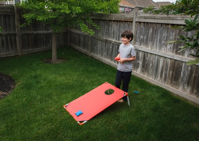 Happy Young Boy Playing A Corn Hole Game In A Fenced Backyard.