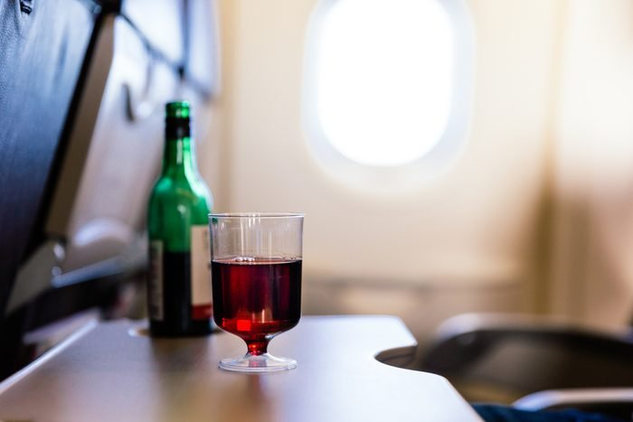Plastic cup of red wine on an airplane tray
