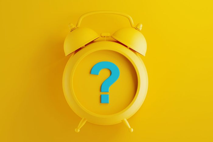 Yellow Alarm Clock with Blue Question Mark on Yellow Background