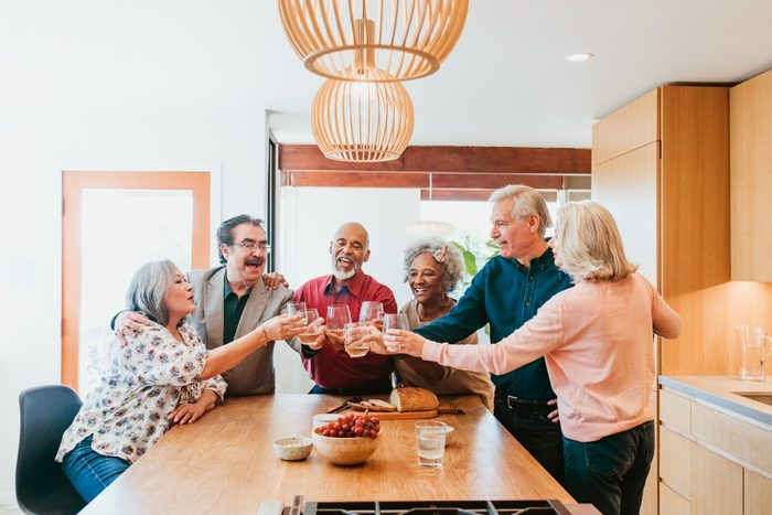 Happy multi-ethnic friends toasting drinks at kitchen island. Retired senior men and women are in kitchen enjoying brunch at home.