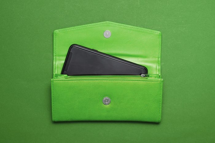 smartphone popping out of open wallet