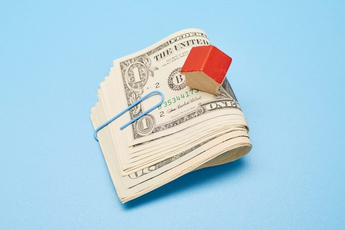 bundle of folded money held with a paper clip and small, wooden house on blue background