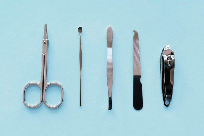 Travel-size manicure tools (scissors, cuticle pusher, tweezers, nail file and nail clippers) on soft blue background