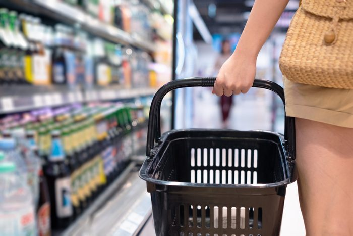 women carrying full shopping basket in grocery store