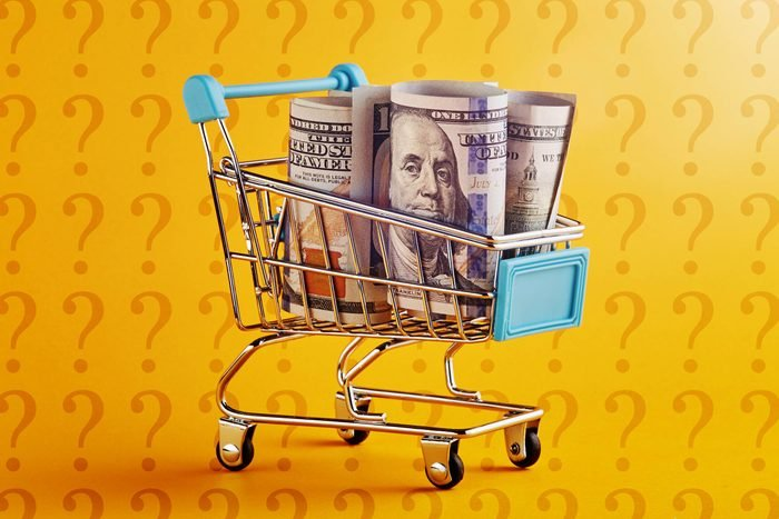 miniature shopping cart with rolled up hundred dollars bills on amazon yellow background with question marks