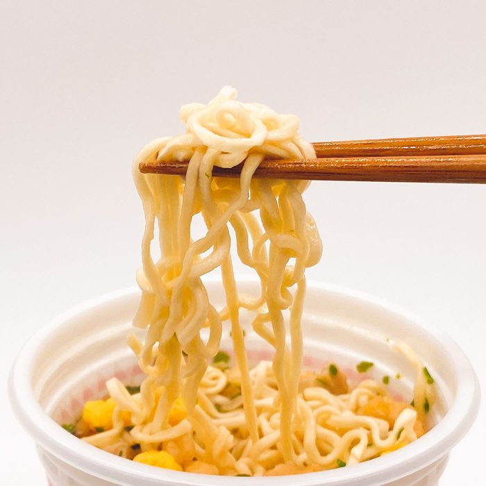 Cup Noodles with chopsticks holding up some noodles