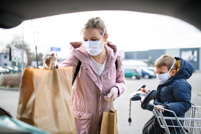 Mother and small son with face mask outdoors putting grocery bags in car.