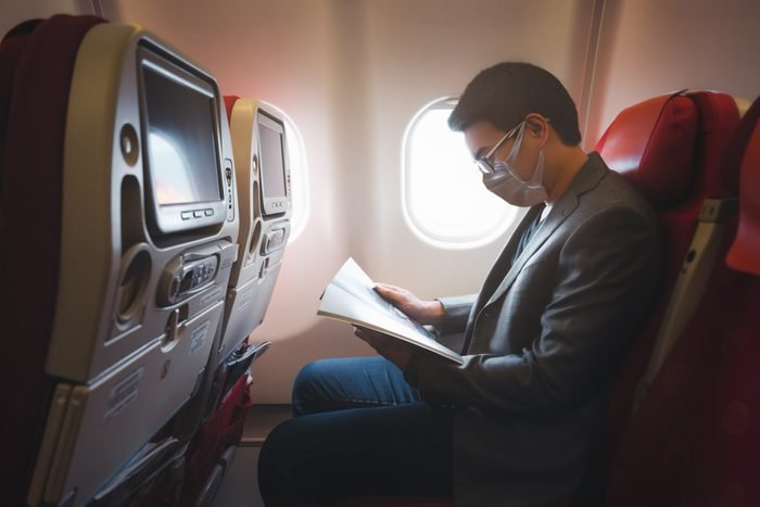 Young asian businessman wearing protective face mask with suit sitting on airplane seat while reading magazine due to Coronavirus or COVID-19 outbreak situation in all of landmass in the world