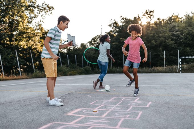 Mother holding plastic hoop while children playing hopscotch