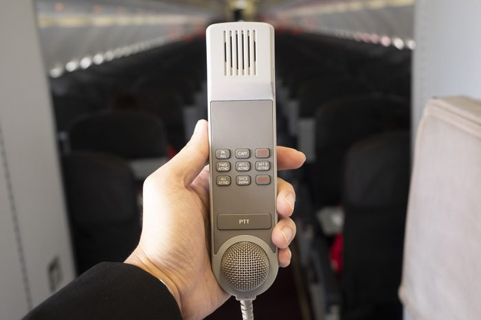 Male cabin crew holding interphone in aircraft cabin.