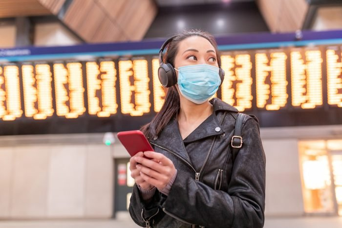 Chinese woman wearing face mask at train station and maintaining social distance - young asian woman using smartphone and looking away with departure arrivals board behind - health and travel concepts