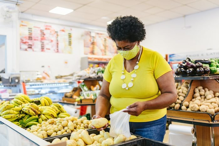 Woman choosing vegetables at the supermarket wearing a face mask