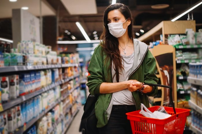 young woman shopping at a grocery store with a face mask
