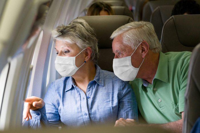 Senior couple traveling by plane wearing facemasks
