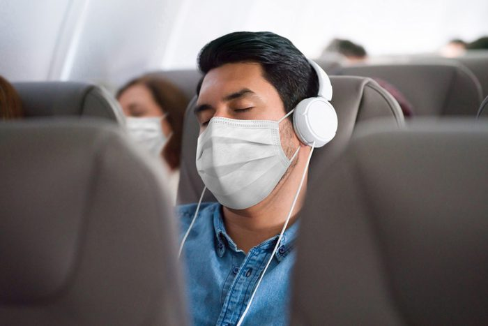 Man traveling and sleeping on the plane wearing a facemask