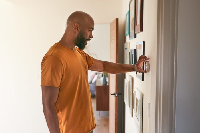 Man Adjusting Digital Central Heating Thermostat At Home in the summer