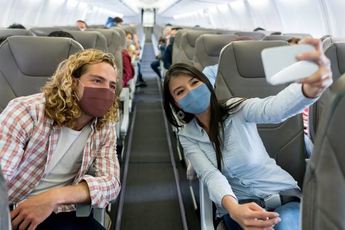 Friends traveling by plane wearing facemasks and taking a selfie