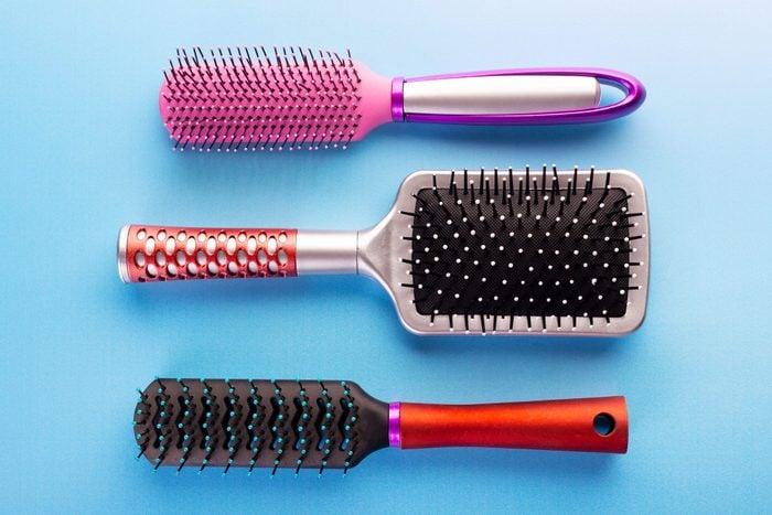 three plastic hairbrushes on blue background