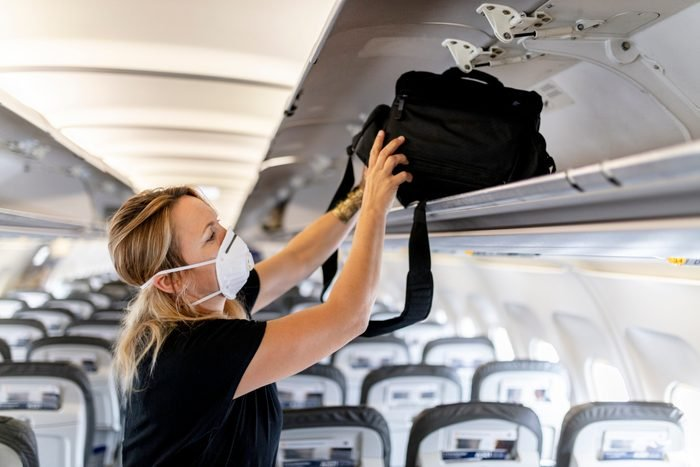 female passenger is wearing an FFP 3 face mask while putting luggage in lockers on plane