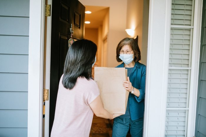 Adult Woman Delivers Groceries to older woman wearing a mask