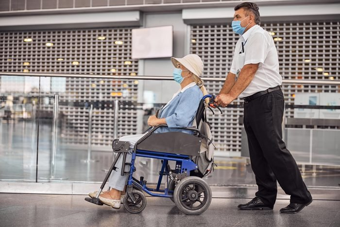 Disabled senior woman being conveyed to a plane