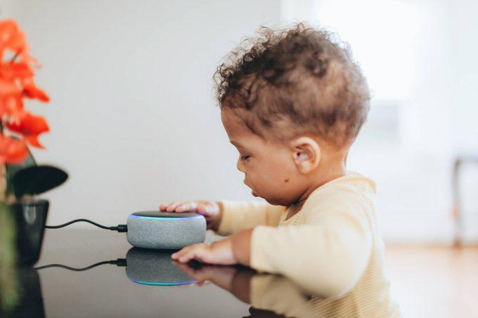 cute baby touching amazon alexa smart speaker device