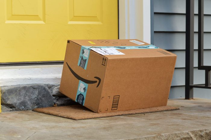 amazon box sitting on a front step near a yellow front door