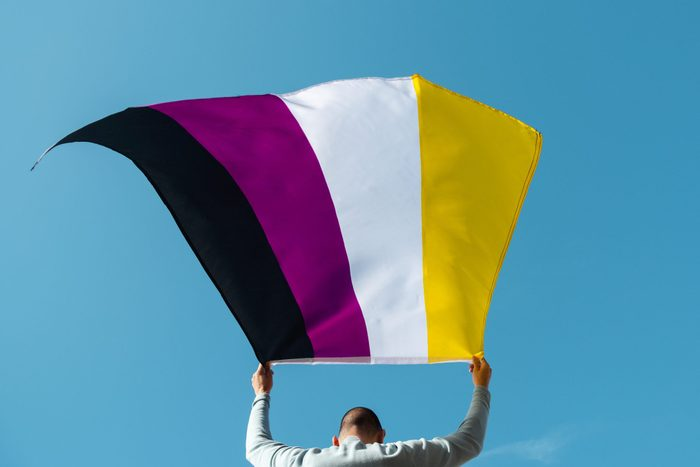 person, seen from behind, waving a non-binary pride flag