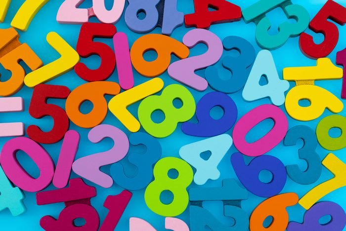 Heap of wooden numbers on blue background