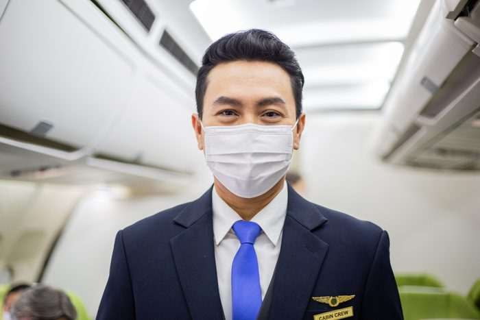 Portrait of Asian steward wearing medical face mask to protect Coronavirus standing in airplane cabin. social responsibility of airline company in new normal adaptation