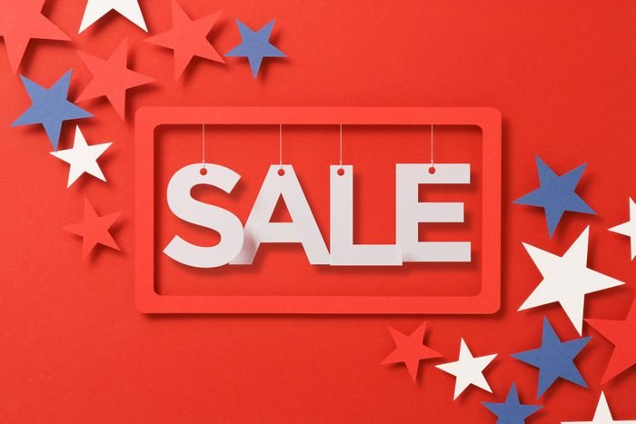 """july themed paper cut red, whtie, and blue stars and a frame with """"SALE"""" text"""