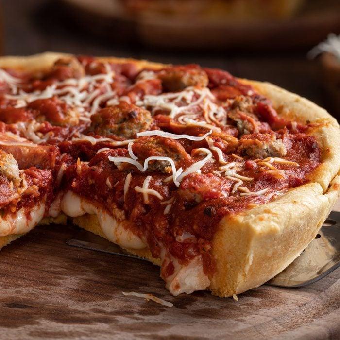 Closeup of a sliced deep dish sausage pizza on a wooden platter