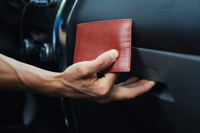 Man hand puts leather wallet in the glove compartment box inside car.