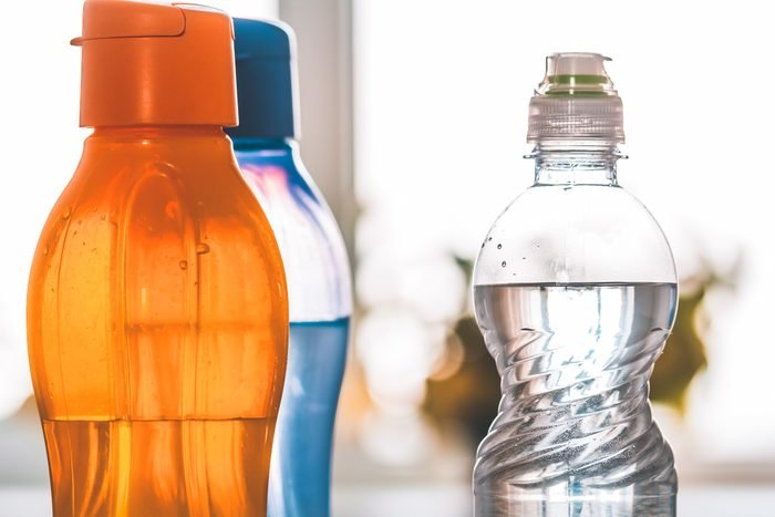 Several colored pet bottles with drinking water close-up. Polypropylene food products
