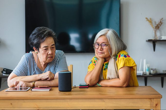 Two women friends using amazon alexa smart speaker while setting in living room at home