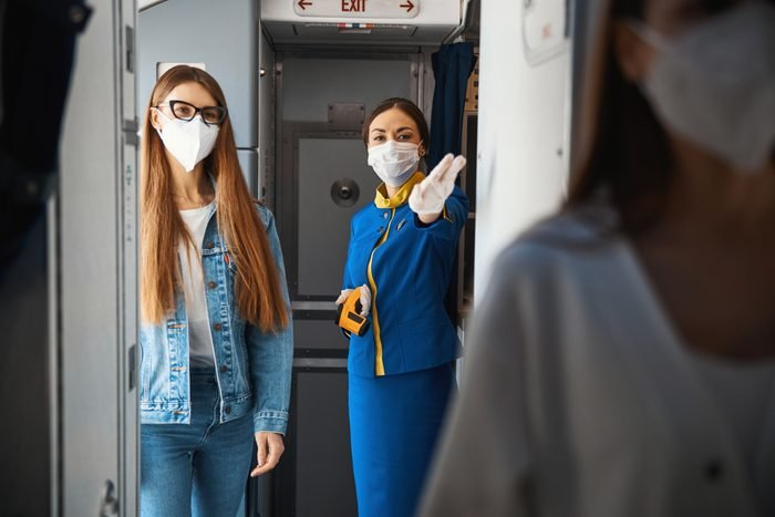 Helpful flight attendant directing woman to her seat in plane