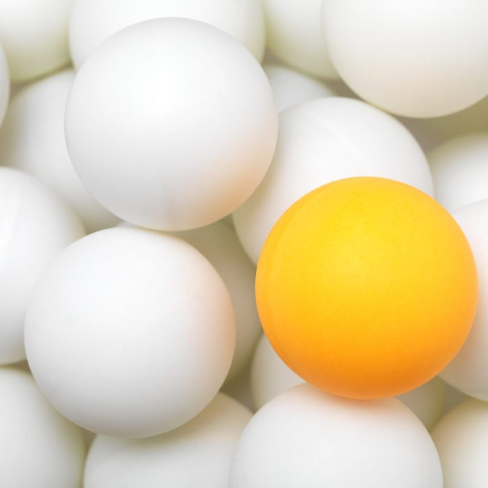 View of white ping balls with an odd yellow ball in it